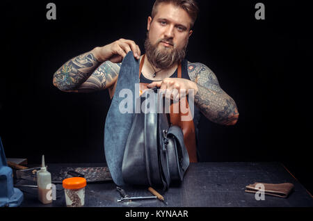 Worker of leather working with leather using crafting tools at a workshop - Stock Photo