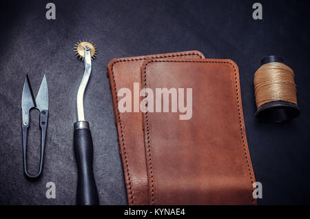 pieces of yellow leather, tools and spool of yellow thread on a black background - Stock Photo