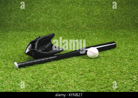 Close-up view of black baseball bat with leather glove and ball on green grass - Stock Photo