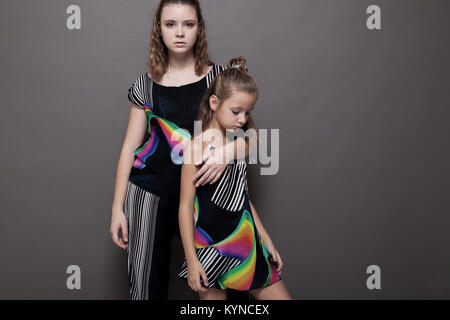 two girls sisters side by side on a grey background - Stock Photo