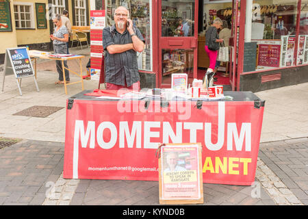 Momentum supporter manning a stall in Ramsgate town centre. The poster is advertising a visit from the Labour Leader, - Stock Photo