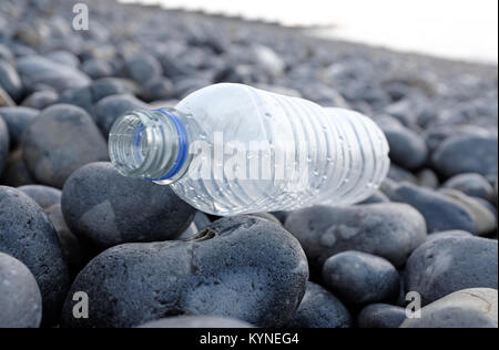 plastic water bottle washed up on shingle beach, sheringham, north norfolk, england - Stock Photo