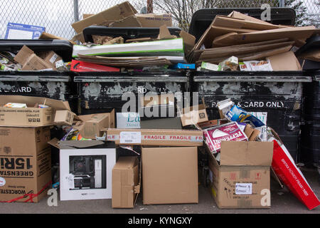 Cardboard and paper recycling overflowing at a council collection point, UK. - Stock Photo