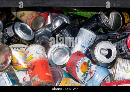 Recycling bin full of tin cans at a council collection point, UK. - Stock Photo