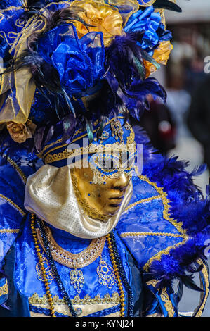 Close-up of masked woman wearing blue and gold costume during the Carnival in Venica, Italy - Stock Photo