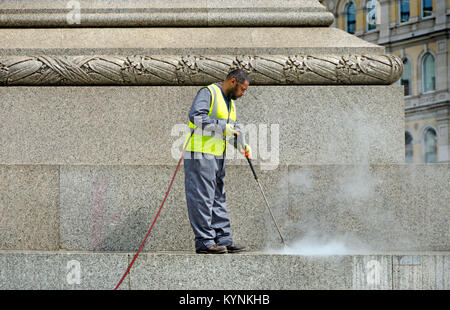 London, England, UK. Man cleaning the base of Nelson's Column with a pressure washer - Stock Photo