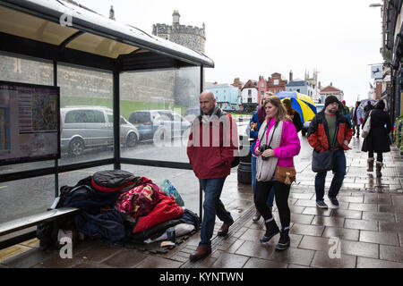Windsor, UK. 15th Jan, 2018. A homeless person sleeps under a bus shelter opposite Windsor Castle in wet weather. - Stock Photo