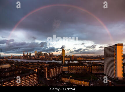 London, UK. 15th Jan, 2018. UK Weather: A massive pink/red rainbow breaks during sunset after a brief rainstorm - Stock Photo