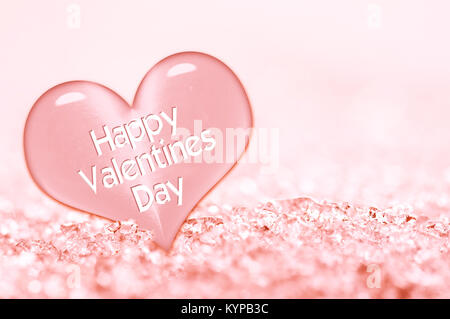 Happy Valentines day greeting card, close up on a pink ice heart in the snow - Stock Photo