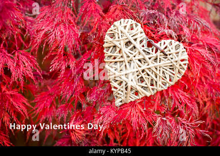 Valentines day card, wooden heart on red maple leaves background - Stock Photo