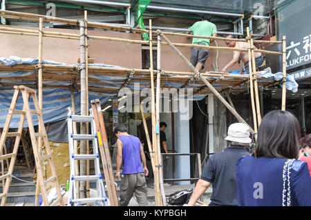 construction workers using bamboo scaffolding in Hong Kong - Stock Photo