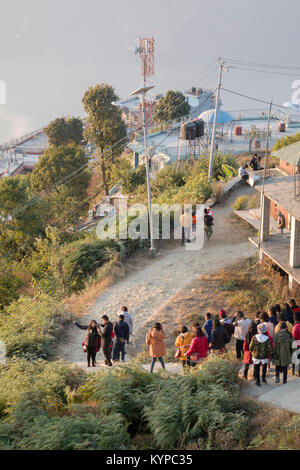 People descend the lookout just after sunrise at Sarankot, Pokhara, Nepal - Stock Photo