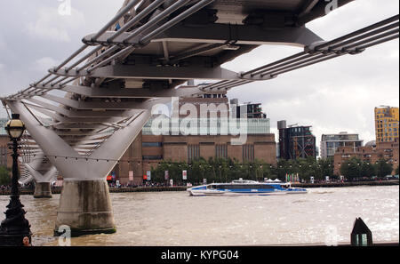View looking across the River Thames, from the north bank, under the Millennium foot bridge towards the Tate modern - Stock Photo