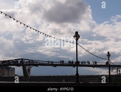 Pedestrians crossing over the Millennium foot bridge over the River Thames, London with classical London street - Stock Photo