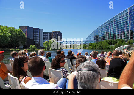 Tourists and holiday makers on a river boat trip around Strasbourg France view and photograph the European Parliament - Stock Photo
