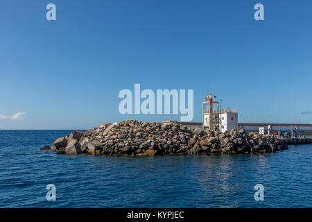 Breakwater blocks in the port of Puerto Rico, Gran Canaria, with the Atlantic Ocean in the background - Stock Photo