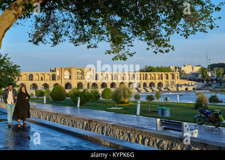 Isfahan, Iran - April 24, 2017: Muslim woman in an Islamic chador walks by the arm with a young smiling man on embankment - Stock Photo