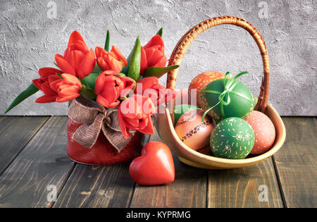 Easter composition with red tulips, wooden heart and a basket of colored Easter eggs on wooden background - Stock Photo