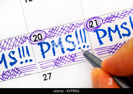 Woman fingers with pen writing reminder PMS in calendar. Close-up. - Stock Photo