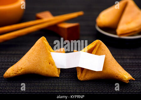 Fortune cookie with clear blank paper strip, another cookie and chopsticks on black napkin background. Close-up. - Stock Photo