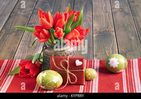 Easter still life with red tulips, wrapped gift and Easter eggs on wooden table - Stock Photo