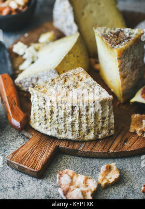 Cheese platter with cheese assortment on wooden board over grey concrete background, selective focus, vertical composition. - Stock Photo