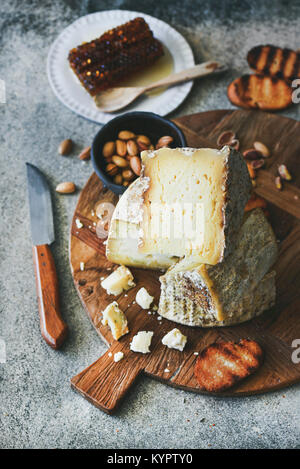 Cheese platter with cheese assortment, nuts, honey and bread on rustic wooden board over grey concrete background, - Stock Photo