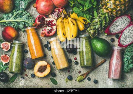 Flat-lay of colorful smoothies in bottles with fresh tropical fruit and superfoods on concrete background, top view. - Stock Photo