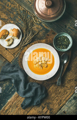 Flat-lay of fall warming pumpkin cream soup with croutons and seeds on board over rustic wooden background, top - Stock Photo