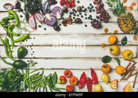 Helathy raw vegan food cooking background. Flat-lay of fresh fruit, vegetables, greens and superfoods over white - Stock Photo