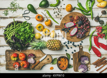 Helathy raw vegan food cooking background. Flat-lay of Fresh fruit, vegetables, greens and superfoods on boards - Stock Photo