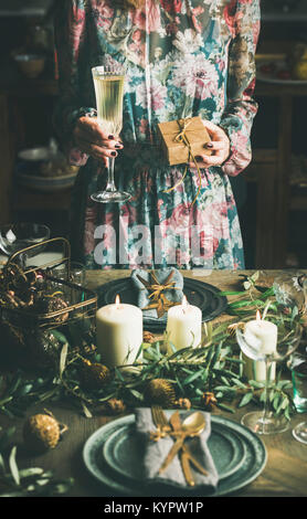 Woman in festive dress holding glass of champaigne and a gift box in her hands at holiday decorated table during - Stock Photo