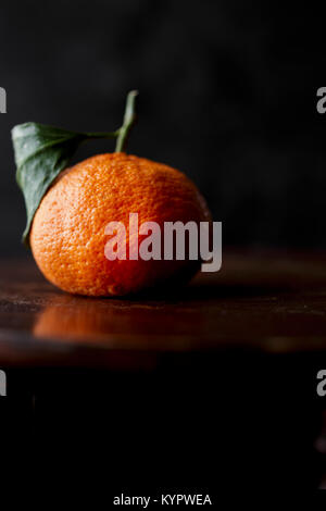 A satsuma on a dark background - Stock Photo
