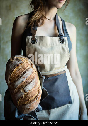 Young woman holding in her hand a fresh loaf of italian bread - Stock Photo