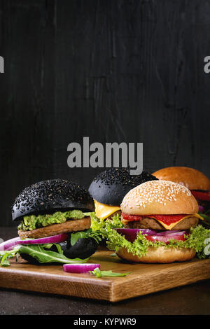 Set of homemade burgers in black and white buns with avocado, tomato sauce, lettuce, arugula, cheese, onion on wood - Stock Photo