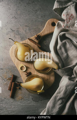Traditional dessert poached pears in white wine served in glass bowls with syrup and lemon zest on wooden serving - Stock Photo
