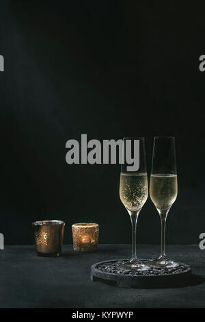 Two glasses of white champagne served on black wooden decorative board with candles over dark texture background. - Stock Photo