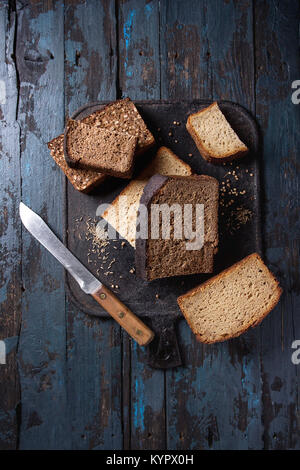 Variety loaves of sliced homemade rye bread whole grain and seeds with knife on black cutting board over old dark - Stock Photo