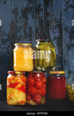 Variety glass jars of homemade pickled or fermented vegetables and jams in row with old dark blue wooden plank background. - Stock Photo