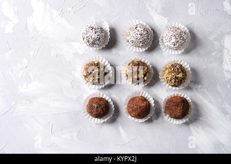 Variety of homemade dark chocolate truffles with cocoa powder, coconut, walnuts in row over gray texture background. - Stock Photo