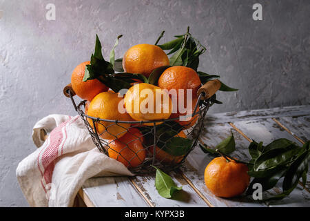 Ripe organic clementines or tangerines with leaves in basket standing with kitchen towel on white wooden plank table - Stock Photo