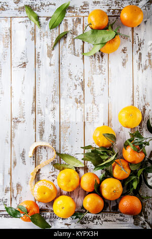Ripe organic clementines or tangerines with leaves over white wooden plank table as background. Top view, space. - Stock Photo