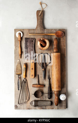 Top view of a group of vintage cooking utensils on a wood cutting board. - Stock Photo