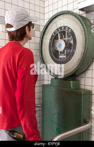 Women standing and weighing herself on a large dial scale. - Stock Photo