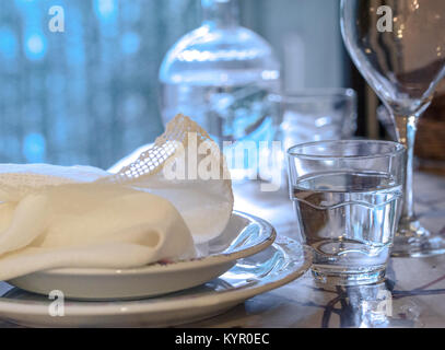 Elegant table set for dinning in a summer with white porcelain dishes, white vintage lace napkin and glassware - Stock Photo