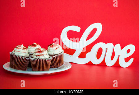 4 chocolate cupcakes with white frosting on a plate next to a sign saying LOVE on a red background with copy space - Stock Photo