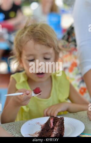 Young girl eating cake at a children's party, The water park, the strand, Townsville, Queensland, Australia - Stock Photo