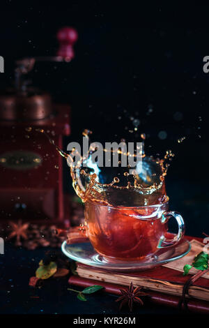 Coffee splash in a glass tea cup with coffee grinder, spices, nuts and coffee beans on a dark background. Action - Stock Photo