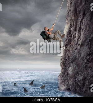 Explorer climbs a mountain with the risk to fall on the sea with sharks - Stock Photo
