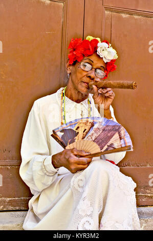 HAVANA, CUBA, MAY 6, 2009. An old woman sitting with a huge cigar in her mouth and roses in her head in Havana, - Stock Photo